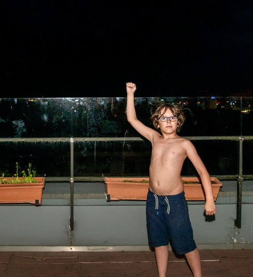 Full length of shirtless boy standing in swimming pool