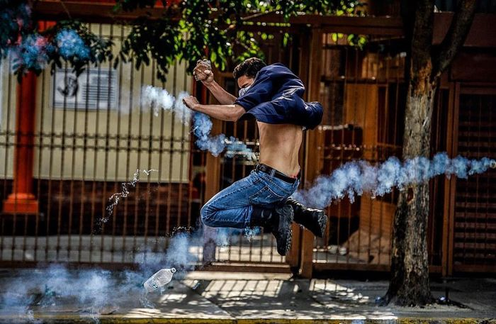 An opposition activists throw a ston to a riot of armed police, Venezuela april 26 17. Motion Real People Freedom Revolution Standing Resist!