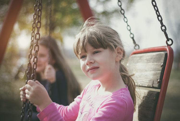 Cute girls sitting on swing at playground