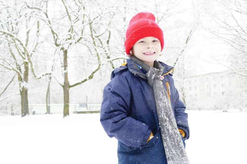 Little Boy Standing On Snow Covered Landscape