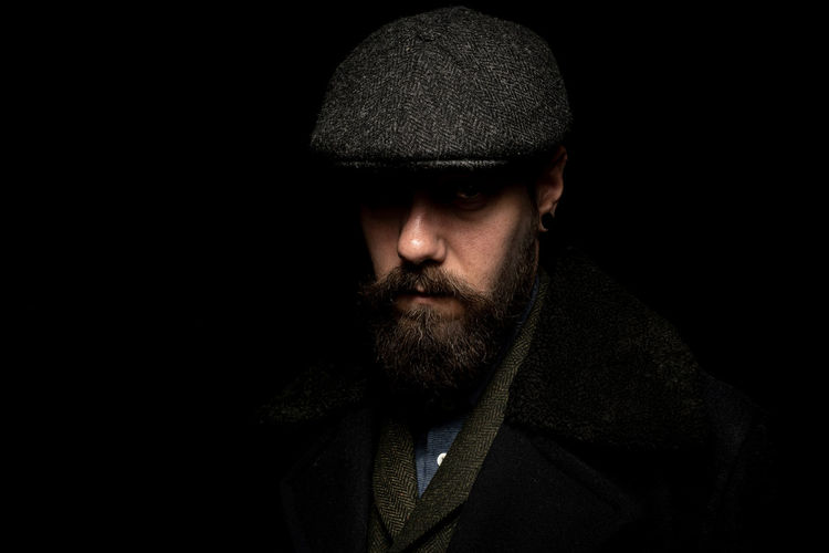 Dark portrait of a bearded male in 1920 style clothing wearing a paper boy cap covering his eyes
