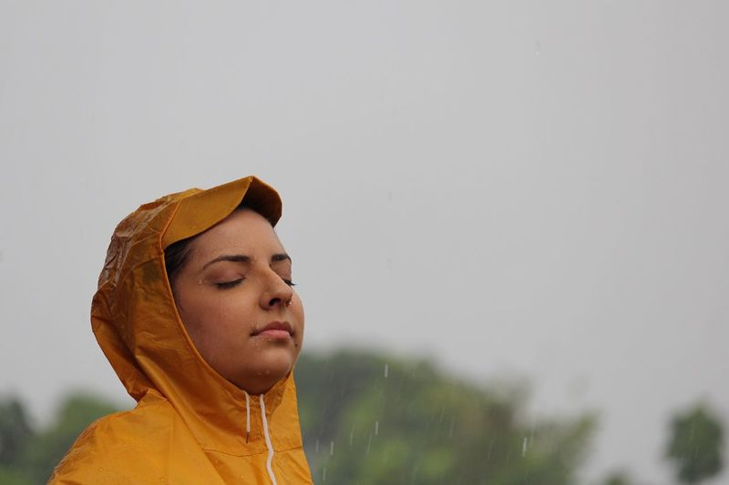 Side view of young woman with eyes closed during rainy season
