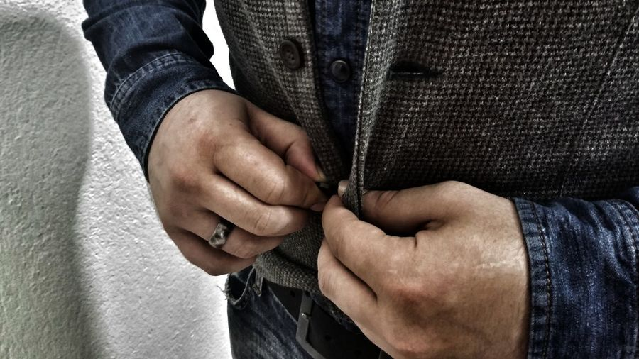 Midsection of man buttoning vest