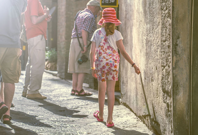 What a beautiful scene near the campo in Siena. An untold story: A young girl ( What will her name be?) with a red hat( fairytale... where is the wolf?) touching a warm mural in late afternoon sunlight. One moment later she disappears in the crowd. Siena. Italy Casual Clothing City Life Day Fairytale  Fairytales & Dreams Focus On Foreground Girl Leisure Activity Lifestyles Mural Outdoors Pink Color Red Shadow Sunlight Untold Stories