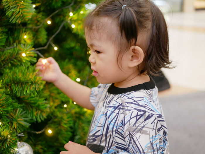 Side view of cute baby girl standing by christmas tree at home