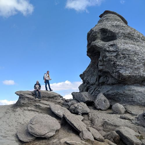 Low angle view of hikers on rock formation against blue sky