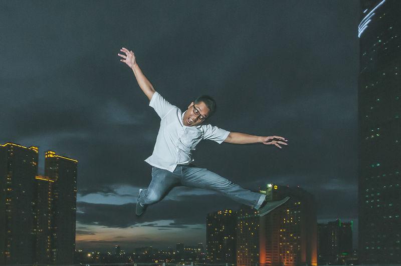 Playful man jumping against illuminated city at dusk