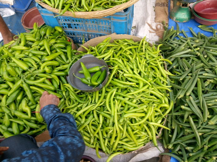 High angle view of man buying vegetables from market stall