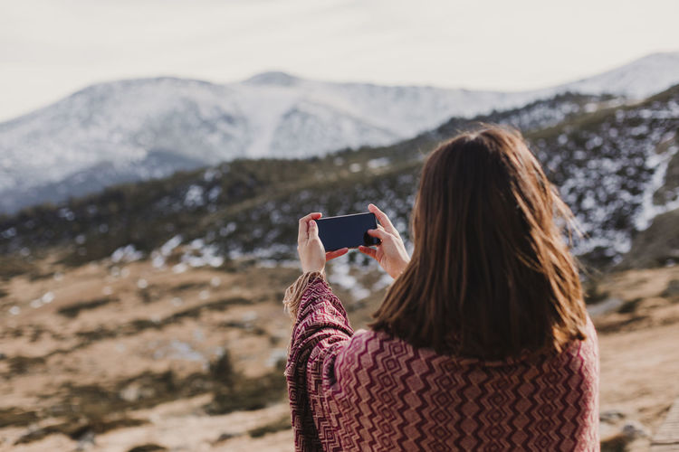 Rear view of woman photographing on mobile phone against mountains and sky
