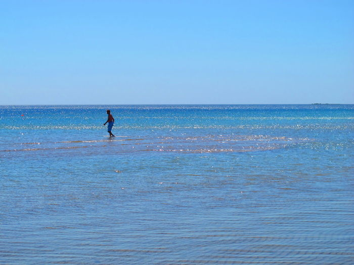 Mature Man Walking In Sea Against Clear Blue Sky During Sunny Day