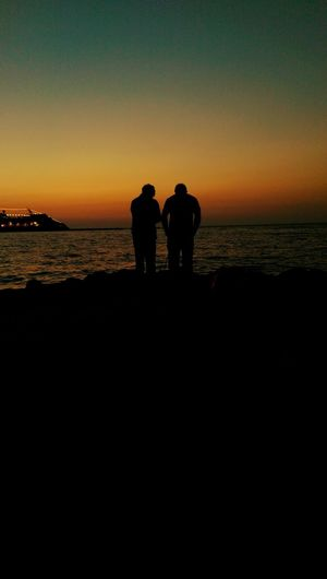 Silhouette Sea Togetherness Men Horizon Over Water Rear View Beach Water Lifestyles Leisure Activity Standing Sunset Full Length Dusk Copy Space Tranquil Scene Clear Sky Looking At View Tranquility Shore