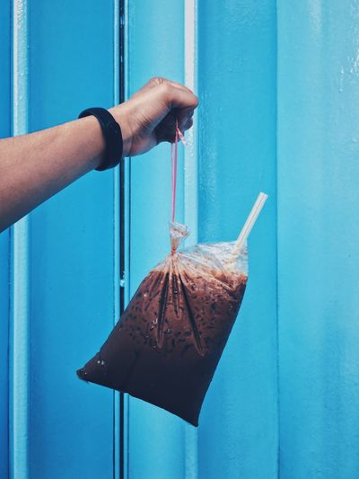 Cropped hand holding smoothie in plastic bag against wall