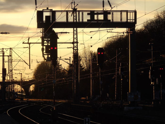 Railway Signals And Electricity Pylons Against Sky