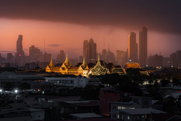 Illuminated buildings in city during sunset