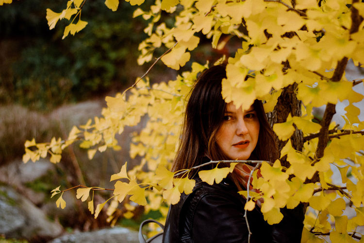 Young Woman Amidst Yellow Leaves