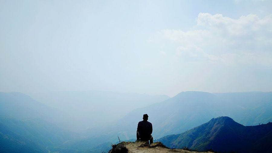 Rear view of man sitting against mountains