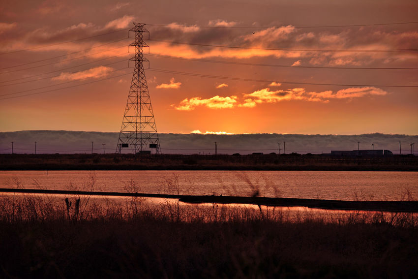 Sunset At Eden Landing 18 The Sun's Last Rays Eden Landing Ecological Reserve Wildlife Refuge Marsh Tidal Wetlands Scenic Salt Pond Lowtide  Mudflats Sunset Silhouettes Sundown Sunset Sunset_collection Sun's Glow Reflections Reflections In The Water Nature Beauty In Nature Nature_collection Fog Marine Layers! Foggy Power Pylon & Lines Telephone Poles & Lines Landscape_Collection Sky And Clouds Native Grasses Trucks On Hwy Horizon Over Water Electricity Tower