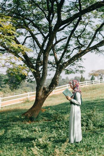 Woman with umbrella on tree