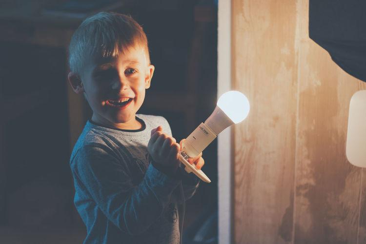 Smiling boy holding illuminated light bulb