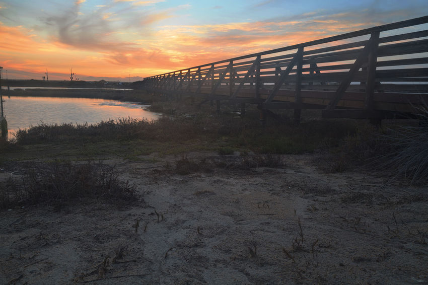 Wooden Boardwalk at sunset, to journey through Bolsa Chica Wetlands preserve in Huntington Beach, California, United States Beauty In Nature Boardwalk Bolsa Chica Huntington Beach CA Orange Color Outdoors Scenics Sky Sunset Tranquil Scene