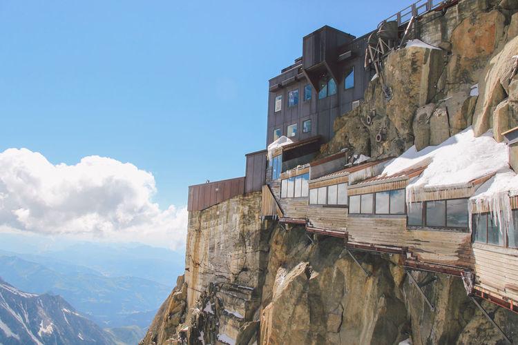 Buildings on rocky mountains at aiguille de midi