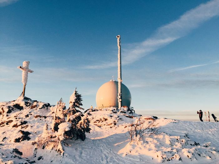 Cross and radar dome on snowcapped mountain peak against blue sky