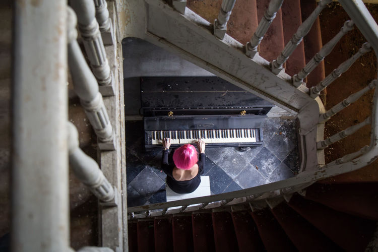 High Angle View Of Woman Playing Piano By Staircase At Home
