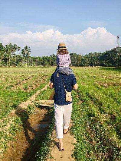 Rear view of father carrying daughter on shoulder at field
