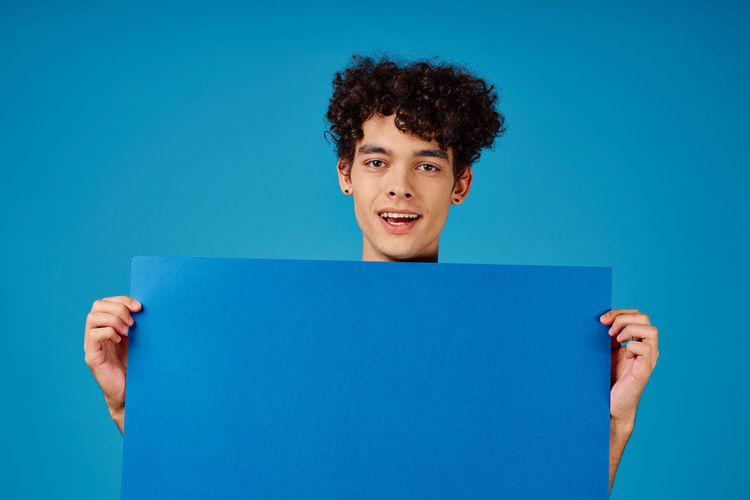 Portrait of teenage boy holding paper against blue background