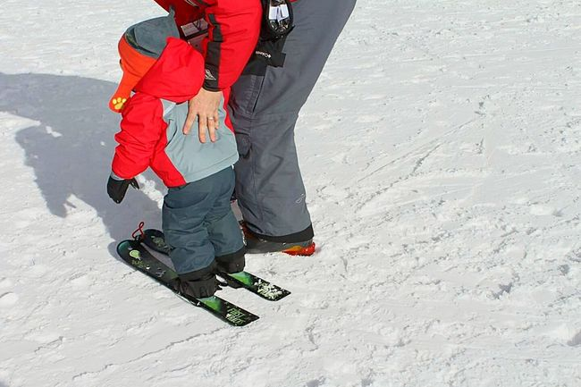 Snow Sports Skiing ❄ View From Behind Child Snow Instructor Ski Instructor Cold Temperature Winter Leisure Activity Winter Sport Togetherness Two People Sunlight Snow Skiing Ski Snowy Mountains Children Playing Ski Slope Ski Resort  Warm Clothing Lifestyles Low Section Outdoors Snow Sport
