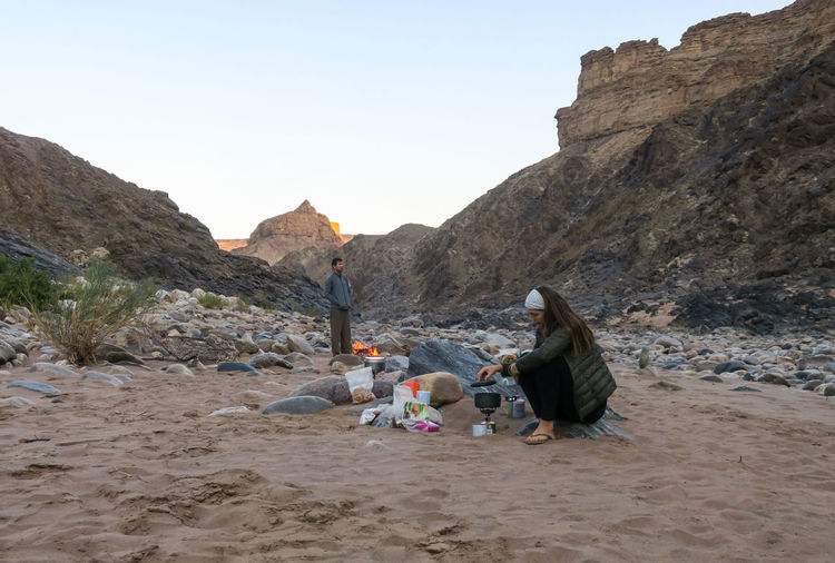 Female hiker prepares dinner on gas stove while friend enjoys the campfire behind her Adventure Beauty In Nature Campfire Camping Cooking Fire Hiker Hiking Mountain Mountain Range Nature Nature Outdoor Outdoor Photography Outdoors People Rock - Object Sand Scenics Travel Two People Wilderness Women