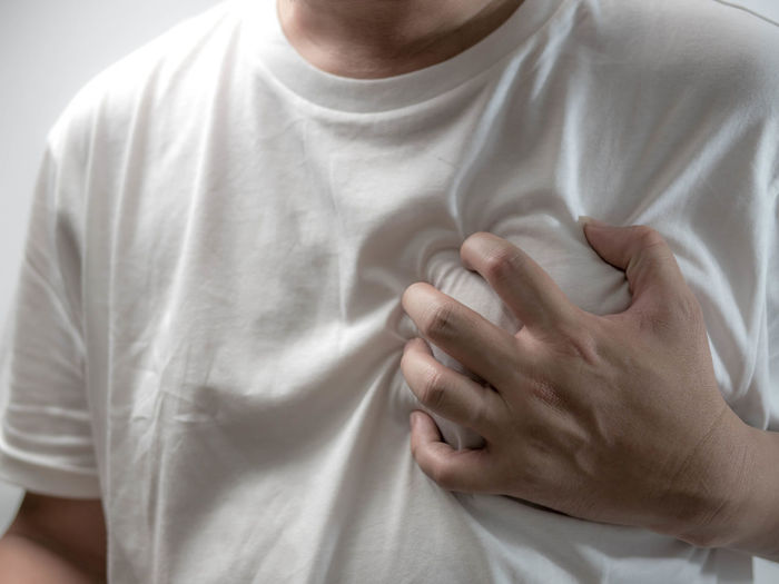 Midsection of man holding aching chest