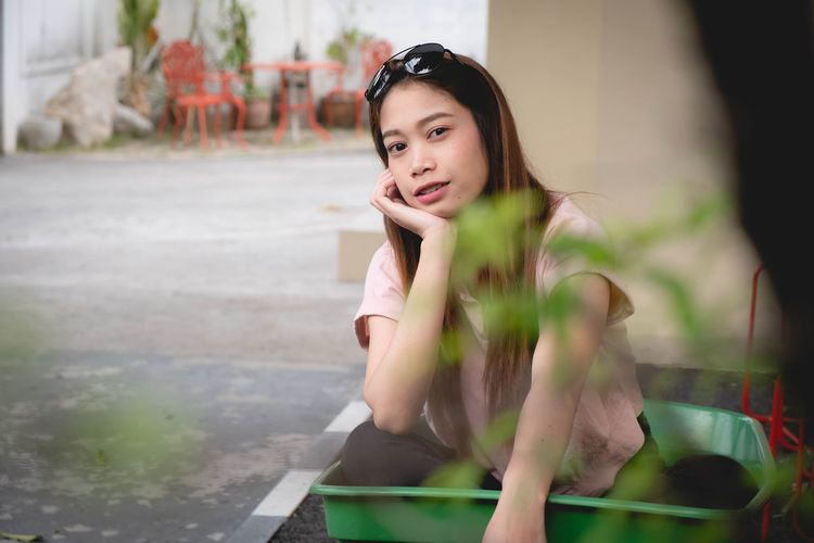 Portrait of young woman sitting in wheelbarrow against wall