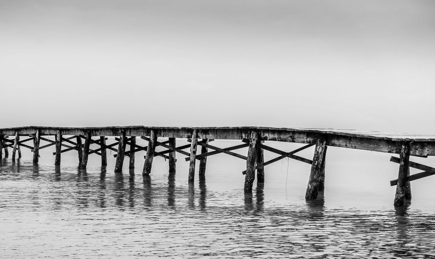 Bridge Over Calm Sea Against Clear Sky