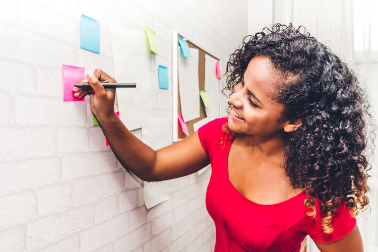 Young fashion designer writing on adhesive notes at home office