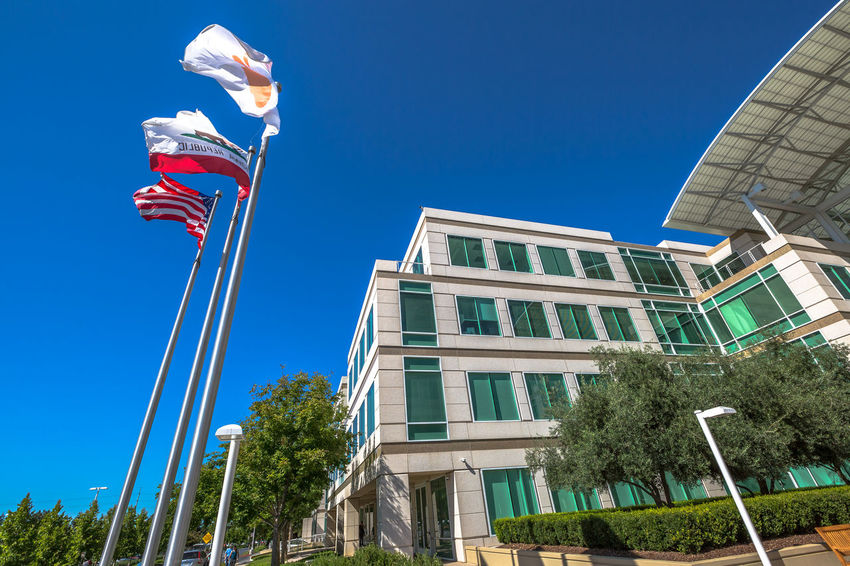 Cupertino, California, United States - August 15, 2016: the Apple world headquarters at One Infinite Loop. Apple is a multinational that produces consumer electronics, personal computers and software. people come from the popular Apple store of Apple Inc Headquarters at One Infinite Loop located in Cupertino, Silicon Valley, California. Apple California IT Mac PC United States Architecture Blue Building Building Exterior Clear Sky Computer Cupertino Day Electronics Industry Flag Headquarter Headquarters Hq IMac27 IPhone Imac Infinite Loop Low Angle View Mobile No People Outdoors Patriotism Sky Store Tree