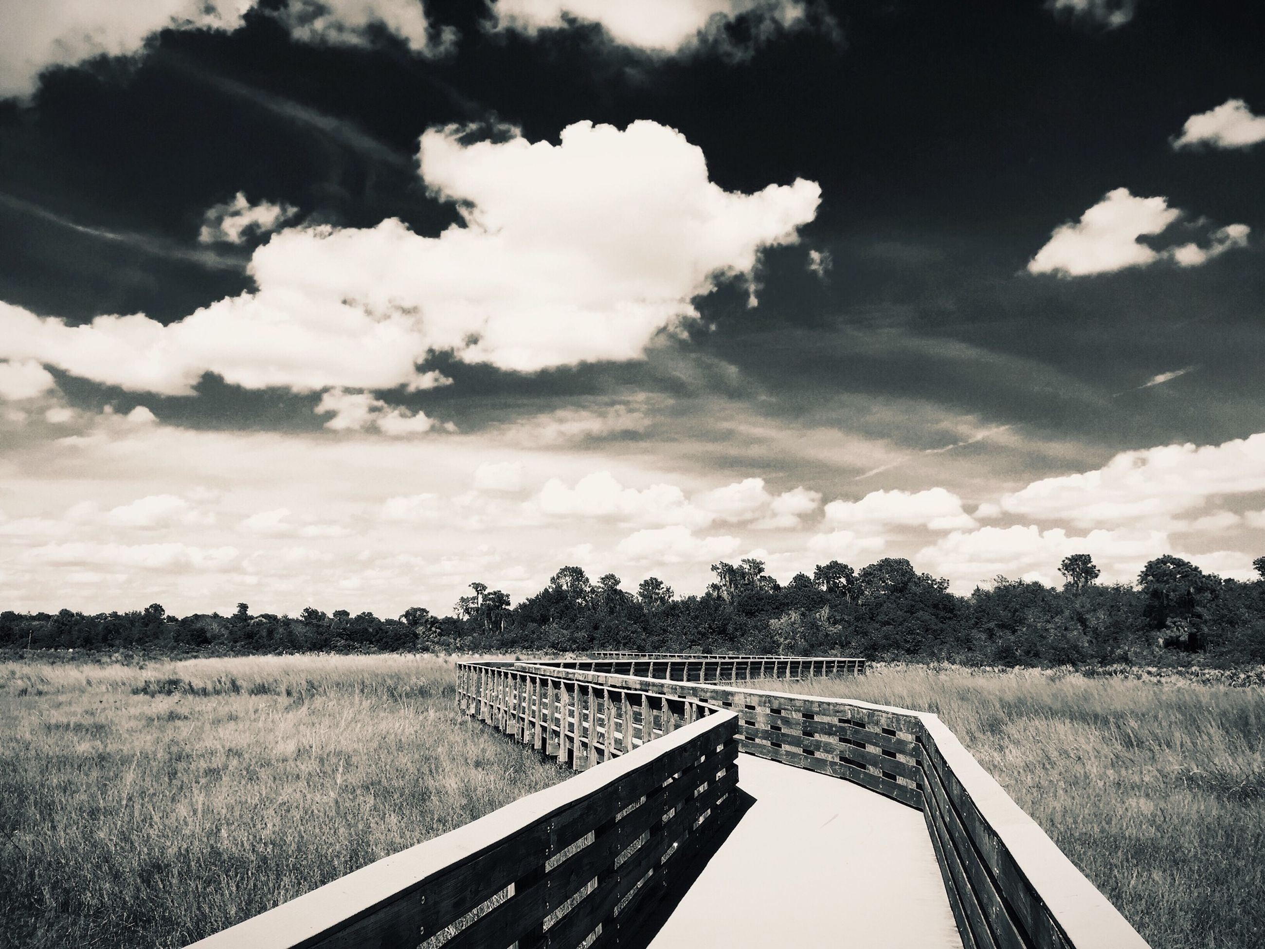 sky, landscape, field, grass, cloud - sky, tranquility, the way forward, tranquil scene, railing, cloud, cloudy, nature, scenics, diminishing perspective, connection, transportation, beauty in nature, long, rural scene, vanishing point