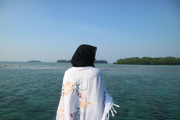 Rear view of woman standing in sea against clear sky