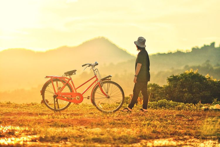 Bicycle Real People One Person Transportation Field Land Vehicle Sky Lifestyles Mode Of Transportation Leisure Activity Men Sunset Nature Outdoors Helmet Standing Full Length Beauty In Nature