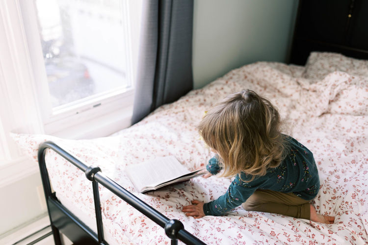 High angle view of girl sitting on bed at home