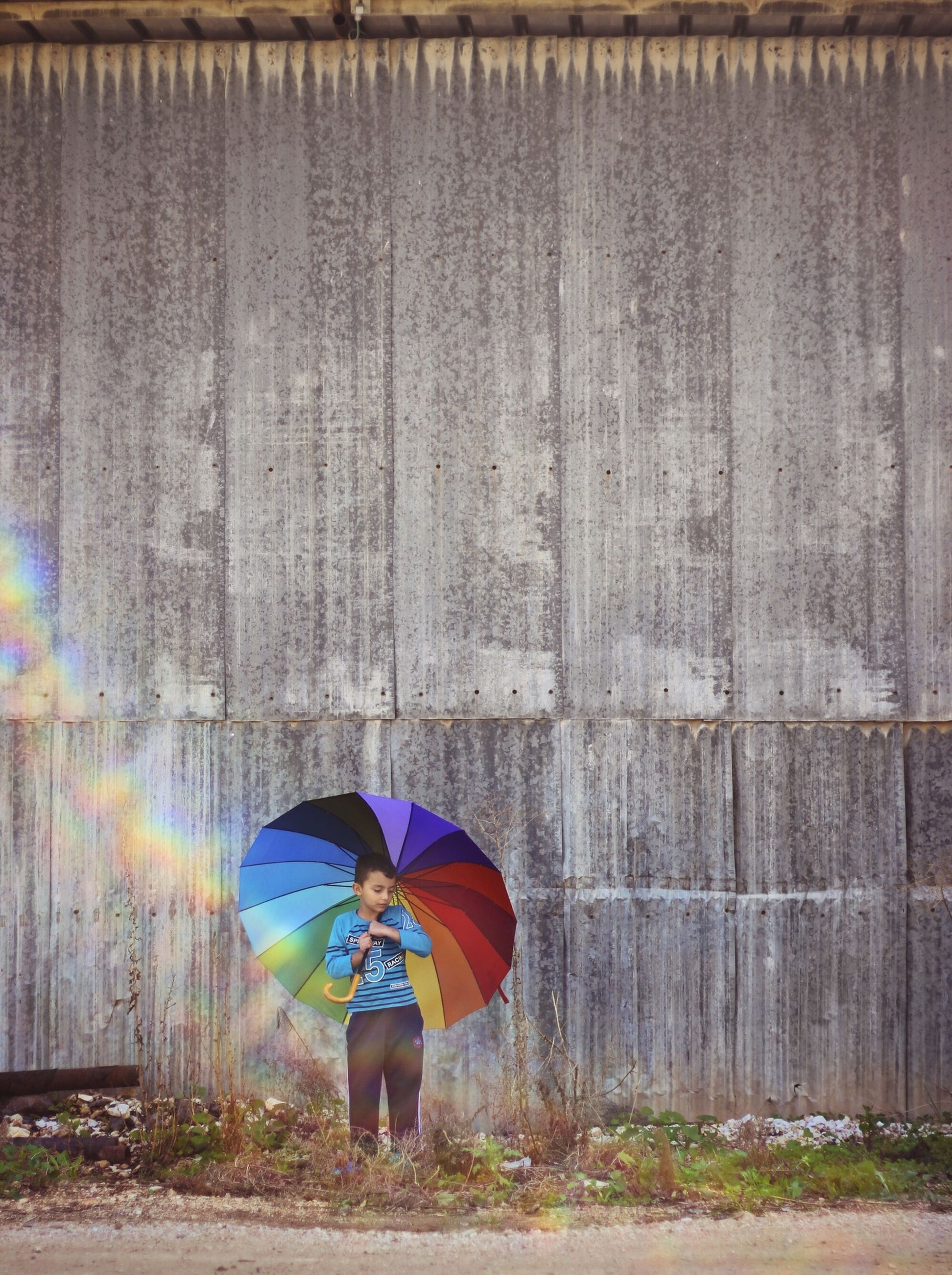 wall - building feature, multi colored, built structure, umbrella, standing, architecture, lifestyles, leisure activity, graffiti, red, art and craft, wall, full length, building exterior, art, outdoors, day, creativity