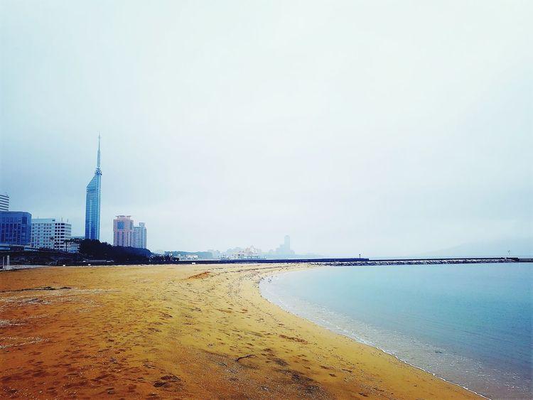 A rainny day in Fukuoka Rainnyday Beach Fukuoka Businesstrip Sea Blue EyeEm Morning FootPrint Nopeople #stillwinter Water Skyscraper Low Tide Calm