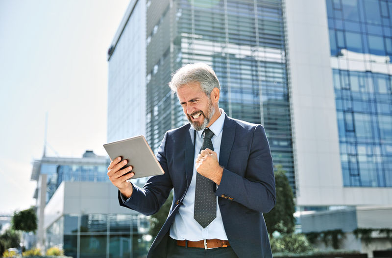 Businessman using digital tablet while standing outside office building