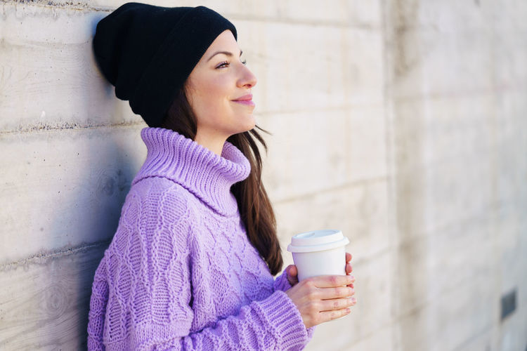 Young woman drinking coffee cup in winter