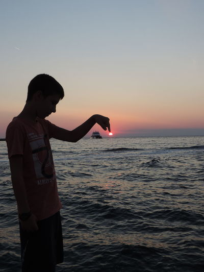 Optical Illusion Of Silhouette Boy Touching Sun Against Sea During Sunset