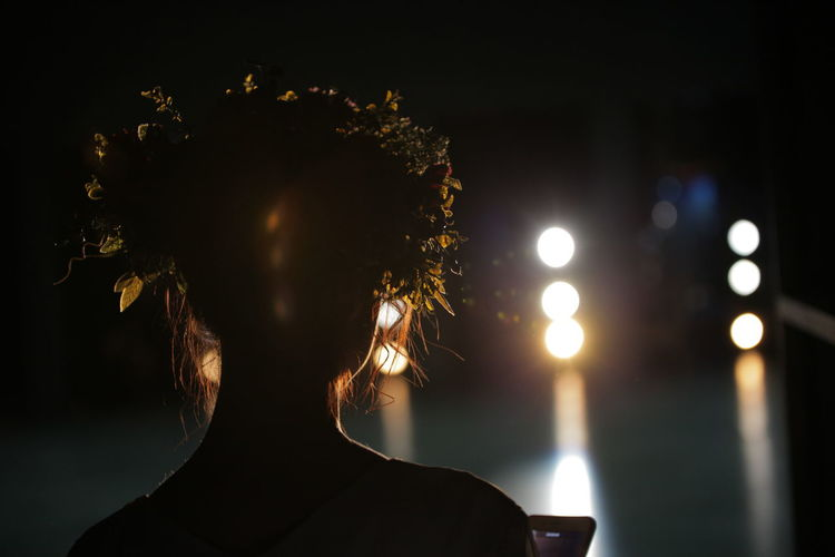 Close-up of silhouette woman against sky and illuminated lights at night