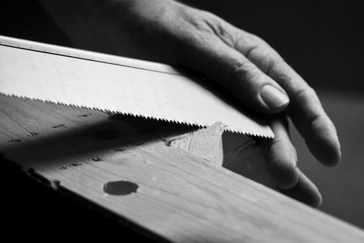Cropped Hand Of Person Shaving Wood In Workshop