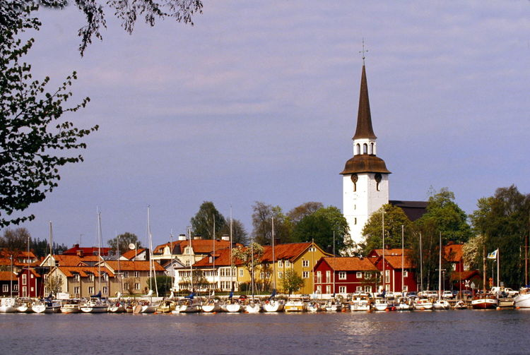 Clock Tower In City By Lake Against Sky