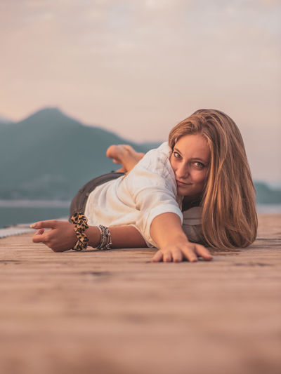 Portrait of young woman relaxing against sky during sunset