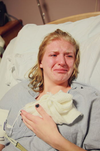 Grieving Mother Baby Bed Broken Heart Crying Grief Holding Home Interior Hospital Indoors  Looking At Camera Loss Miscarriage Mother Pain Portrait Premature Real People Sadness Young Adult
